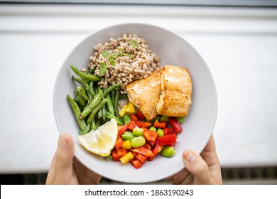 Hands holding salmon and buckwheat dish with green beans, broad beans, and tomato slices. Nutritious dish with vegetables and fish from above. Healthy balanced diet
