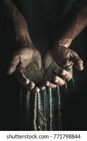 Hands holding sand in dark background.