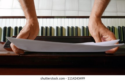 hands holding sheet music, piano art musical concept