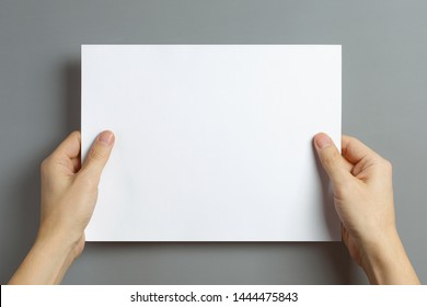 Hands holding a sheet of white paper on gray background