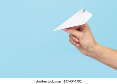 Hands holding the sign of paper airplane or message on blue studio background. Negative space, advertising. Social media, showing meaning, communication