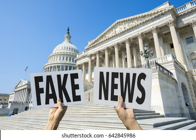 Hands holding signs protesting fake news coverage in front of the Capitol Building in Washington DC, USA