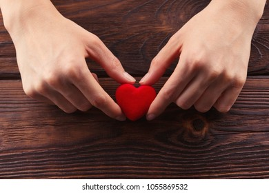 Hands holding small bright red heart on wood background