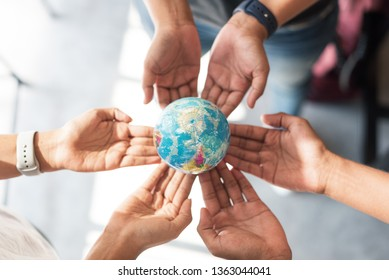 Hands holding small globe, concept save the world
