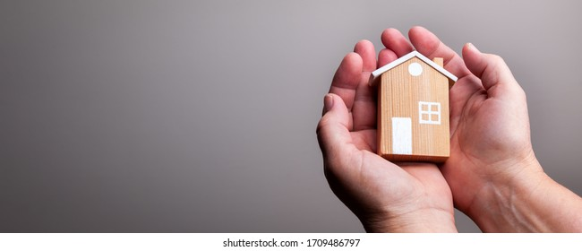 Hands Holding Small House/ Protection Concept