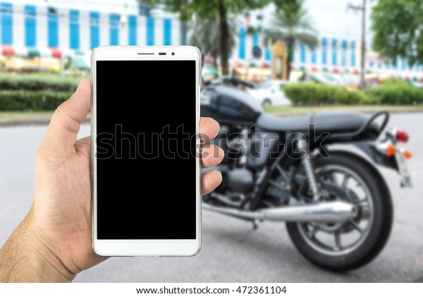 hands holding smart phone with blur motorcycle parking.