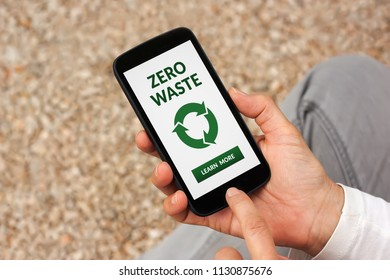 Hands holding smart phone with zero waste concept on screen. All screen content is designed by me