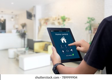 hands holding smart tablet with app smart home on blurred home living room as backgrounds