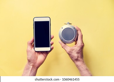 Hands holding smartphone and bluetooth speaker