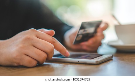 Hands Holding A Smartphone and Debit Card