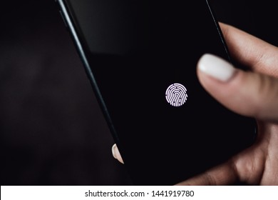 Hands holding smartphone with fingerprint scanner in the screen on black background