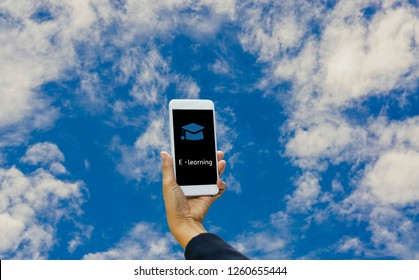 Hands holding smartphone online and e-learning, with book and hat icon, Background isolated blue, concept freedom of online and internet literacy education with boundless education