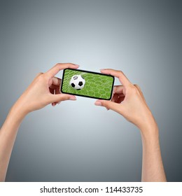 Hands holding smartphone with soccer ball background