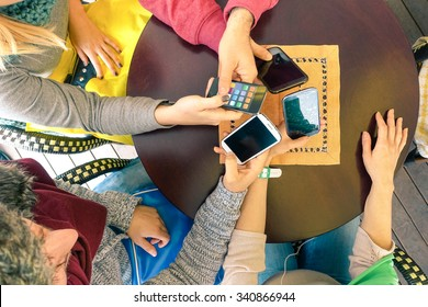 Hands holding smartphone top view - Mixed  group of friends having fun with mobile - Young students playing with telephone -  Concept of modern lifestyle and technology - Focus on mobile phones