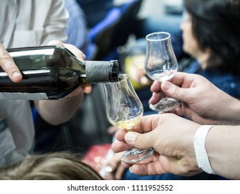 Hands holding a snifter glass filled with whisky, whisky tasting event