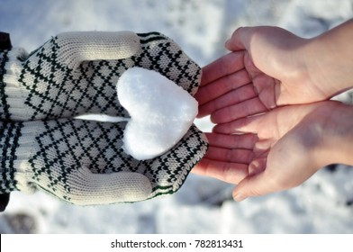 Hands holding a snow heart and sharing love