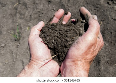 Hands holding soil in agricultural field