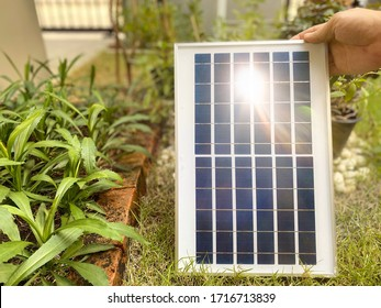 Man's hands holding Solar panel at a house with sunlight. Concept sustainable resources and reduction of expenses on electricity
