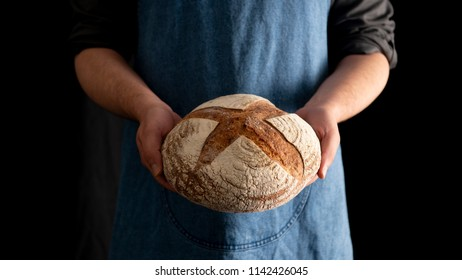 Hands holding a sourdought rye bread on a black background