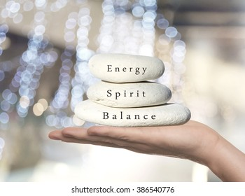 Hands holding stack of pebbles with Balance, Spirit and Energy written on the top stone.