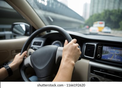 Hands holding steering wheel driving car on road