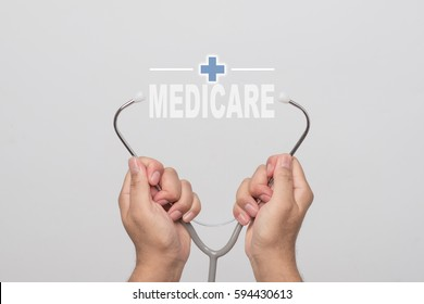 """Hands holding a stethoscope and word  """"MEDICARE"""" on gray background. concept Healthy."""