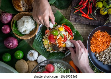 "Hands holding sticky rice to eat with Thai papaya salad or what we call "" Somtum "" in Thai with ingredients. The famous local Thai street food with hot and spicy dish. Food stylish photography concept"