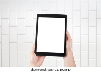 Hands holding tablet and brick tiles stacked in the background. Internal room such as a hospital, spa, bathroom, butcher's shop or toilet. Isolated screen with copy space.