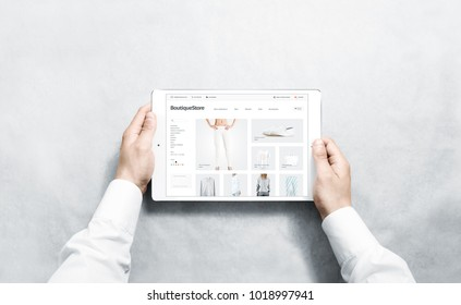 Hands holding tablet with fashion webstore mock up on screen, isolated. Clothing web page interface mockup. Internet website online template on the device display.