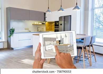 Hands holding tablet with kitchen interior sketch. In background real finished kitchen interior design. Kitchen presentation. Dinning table. Home Interior Design Software Programs.Project management.