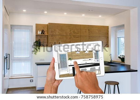 Hands Holding Tablet With Kitchen Interior Sketch. In The Background Real  Finished Kitchen Interior Design