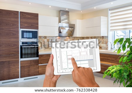 Hands Holding Tablet With Kitchen Interior Sketch. In The Background  Finished Kitchen Interior Design.