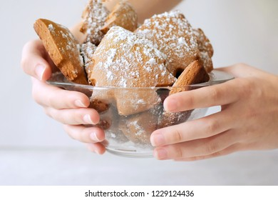 Hands holding tasty traditional christmas cookies in glass bowl. Holiday gingerbread like a new year trees with sugar icing on neutral background