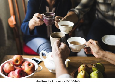 Hands holding tea cups clinking together