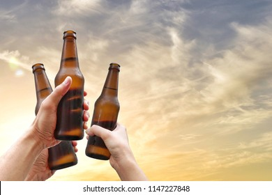 Hands holding three beer bottles and happy enjoying harvest time together to clinking glasses at outdoor party on beautiful sunset background.Celebration drinking beer.