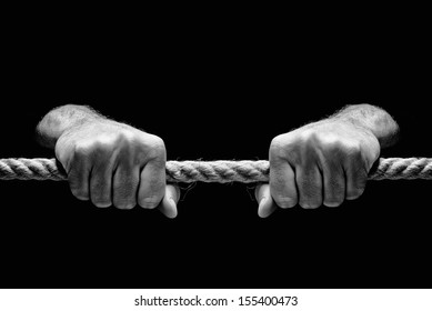 Hands holding tight rope on dark background. Salvation or redemption concept.