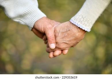 Hands holding together on a natural background