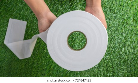 Hands holding a Toilet Paper or Toilet Rolls with an artificial grass texture background. Selective focus.