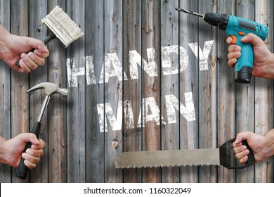 hands holding tools on wooden background with handyman  writing on it
