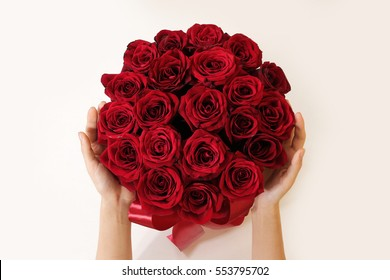 Hands holding top view of luxury bouquet of red roses top view with red bow. On Valentine's day holiday