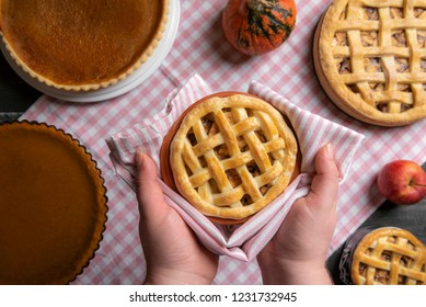 Hands holding a tray with an apple pie, above a kitchen table full of various pies, pumpkin pies, and apple pies, on a towel. Home baked pastry.
