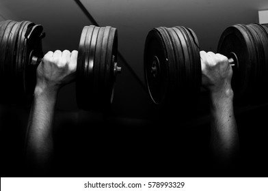 Hands holding two dumbbell weights.