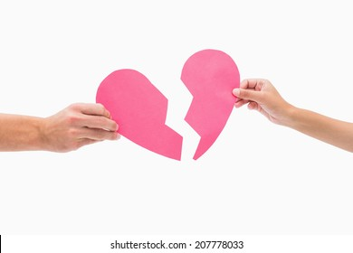 Hands holding two halves of broken heart on white background