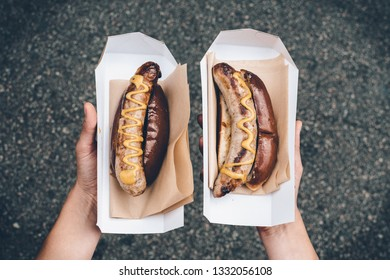 Hands holding two hot dogs covered with mustard