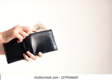 Hands holding a wallet and bring Thai banknotes value 1000 and 500 Baht out from it for paying on white background.