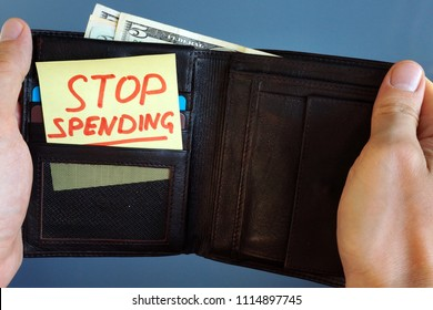 Hands holding wallet with stick Stop spending.