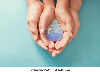 Hands holding water drop,world water day,clean water and sanitation, hand sanitizer and hygiene for covid pandemic, vaccine,family washing hands, CSR, save water, clean renewable energy concept