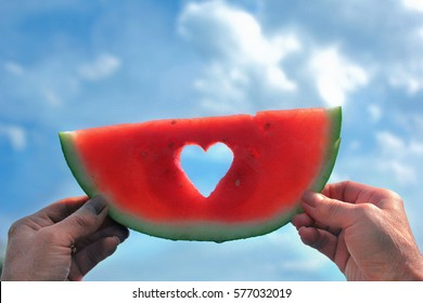 Hands holding a watermelon slice with heart center towards the sky.