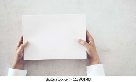 Hands holding white blank paper