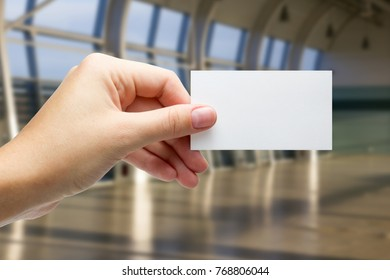 Hands holding a white business visit id card, gift, ticket, pass, present showing close up on blurred blue background. Copy space for ad text